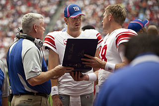 Eli Manning reviews notes during NFL game